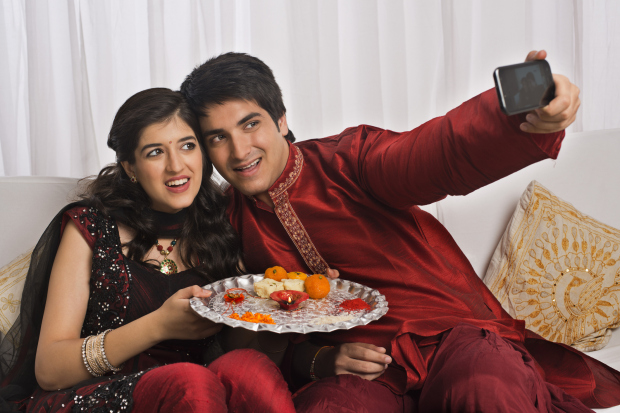 Brother and sister taking a picture of themselves with a mobile phone at Raksha Bandhan
